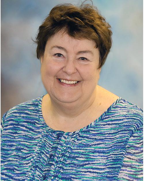 Photo of Linda Keilman smiling at camera has short brown hair and dark eyes on portrait backdrop