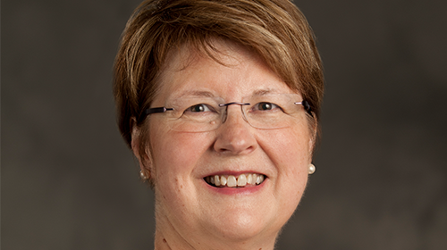 Photo of Emily Wilson has short hair and glasses smiling at camera on portrait backdrop