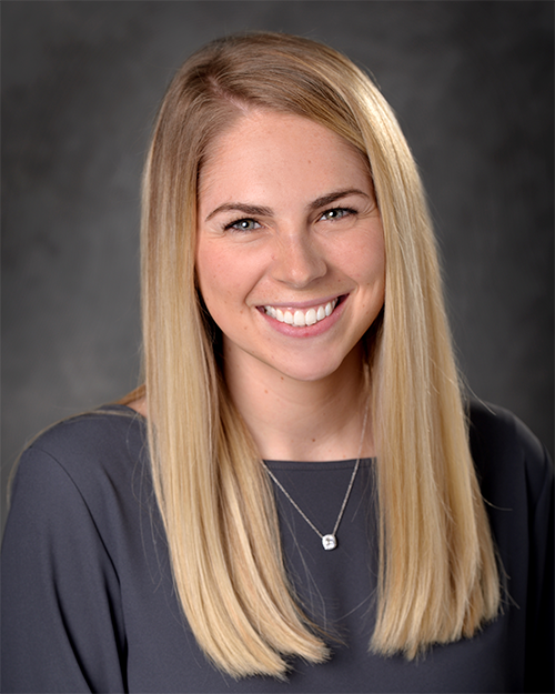 Photo of Jessica Lincoln with long blonde hair and blue eyes smiling at camera on a portrait background