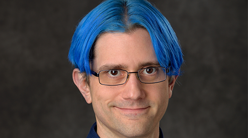Photo of Robert Crawley smiling at camera has short blue hair and glasses on a portrait backdrop.