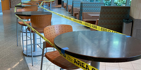 Tables in Bott lobby blocked off with yellow caution tape.
