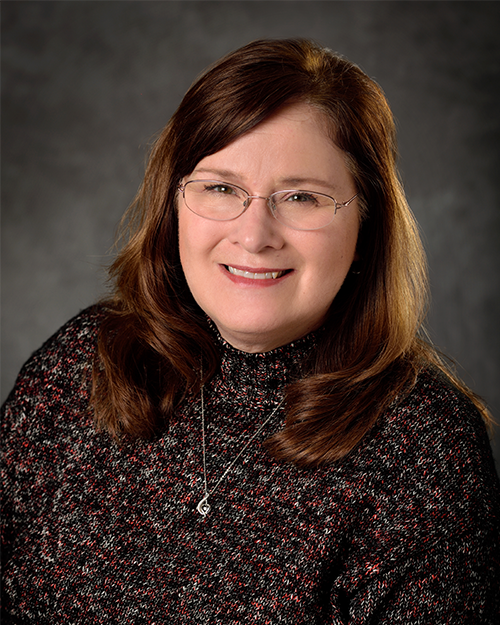 Photo of Laurel Switzenberg smiling at camera has brown hair and eye with glasses on portrait backdrop.