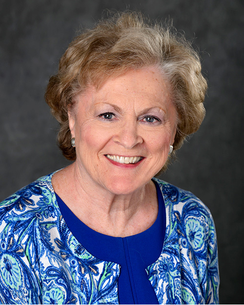 Photo of Nancy Artinian has short blonde hair and soft eyes smiles at camera on a portrait backdrop