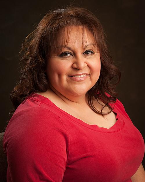 Image of Rosalva Aguilar with brown, long curly hair, and straight bangs smiling at camera