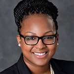 Photo of Assistant Director of Student Affairs Krystal Jones in a suit smiling brightly at camera.