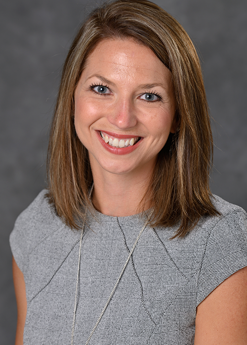 Photo of Crista Reaves on portrait background, light brown hair and blue eyes smiles at camera.