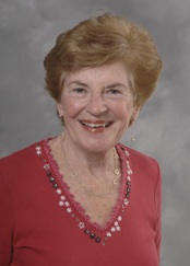 Image of Brigid Warren smiling at camera wearing a pink v-neck with a long-sleeved shirt. There are black and white flowers along the v-neck.