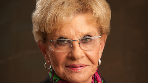 Photo of Jacqueline Wright with short blonde hair and glasses smiling at camera on portrait backdrop