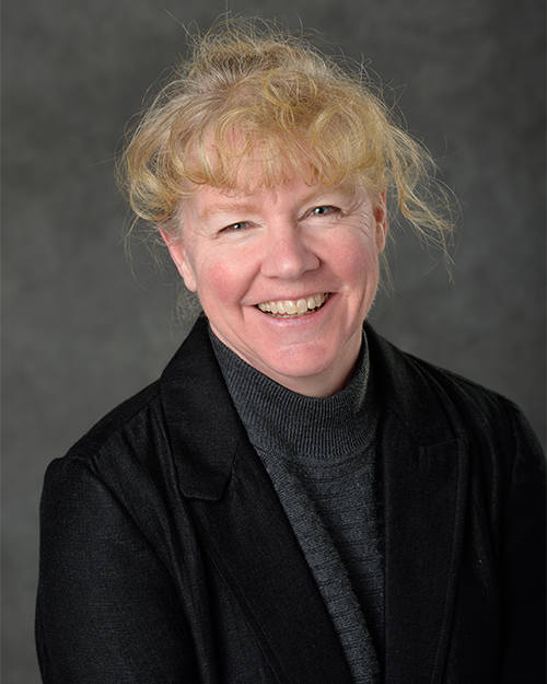 Image of Cynthia McNerlin smiling wearing a black suit with blonde hair