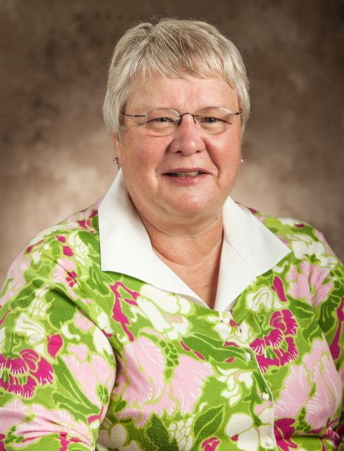 Photo of Sandra Geller smiling at camera on portrait background has white hair and glasses with stud earrings on